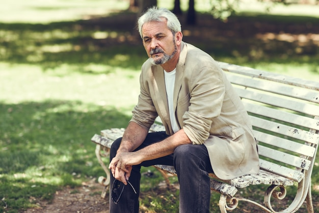 Un homme mature pensif assis sur un banc dans un parc urbain.