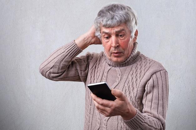 Un homme mature sérieux tenant un smartphone dans sa main en regardant attentivement l'écran