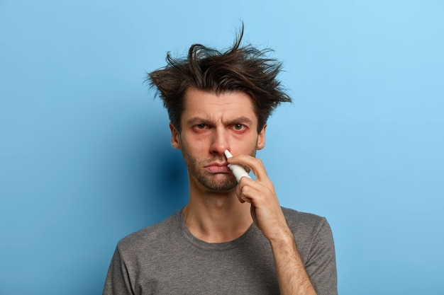 Un homme en mauvaise santé traite le nez avec un spray, souffre de rhinite allergique, a les yeux rouges larmoyants, les premiers symptômes du virus, pas de dépendance aux médicaments, isolé sur un mur bleu. traitement de la sinusite