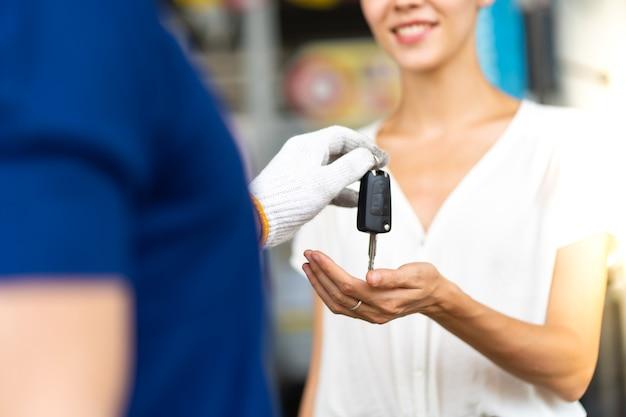 Homme mécanicien d'âge moyen avec barbe donne la clé de voiture à une cliente à la station d'entretien automobile et garage de service automobile