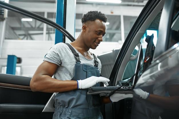Homme mécanicien à l'aide d'un ordinateur portable à l'auto avec capot ouvert en atelier mécanique
