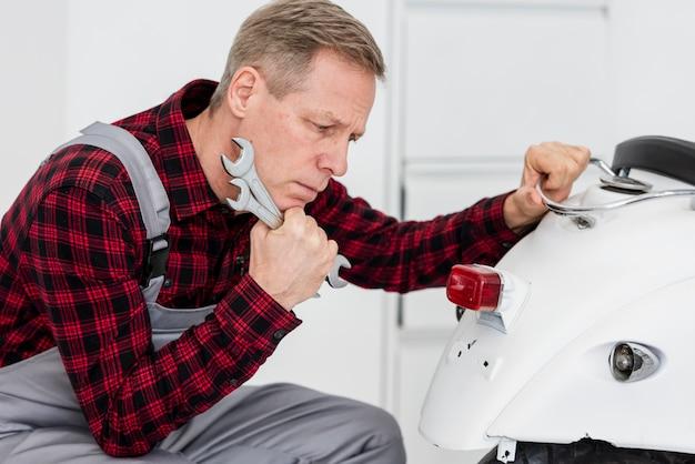 Homme mécanicien à angle élevé travaillant