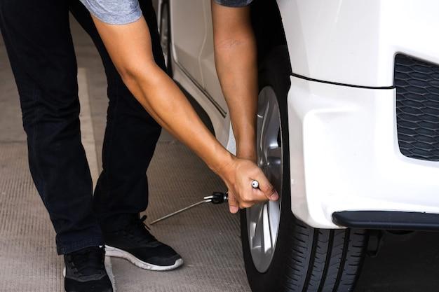 Un homme ou un mécanicien automobile change le pneu ou l'entretien de la voiture avant de voyager pour des raisons de sécurité.