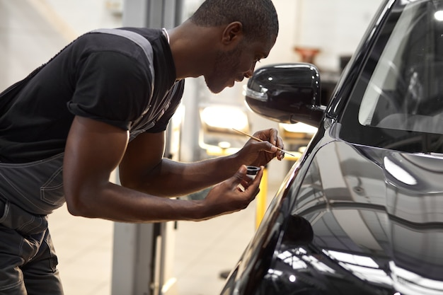 Homme de mécanicien automobile confiant à l'aide d'un pinceau pour peindre une voiture