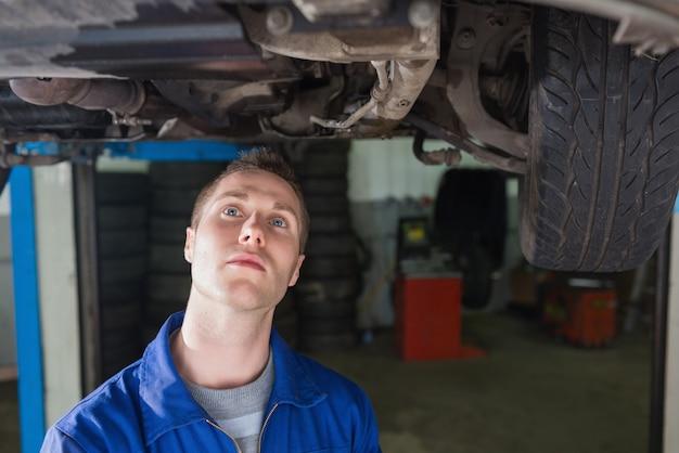 Homme mécanicien examinant sous voiture en atelier