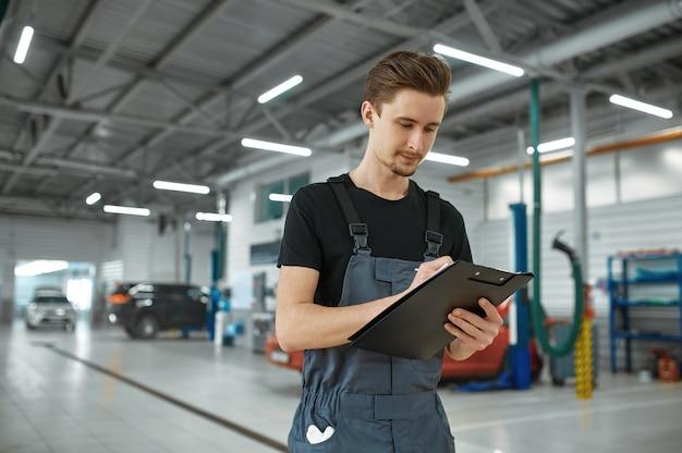Homme mécanicien avec liste de contrôle en atelier mécanique