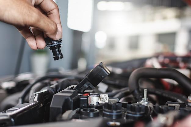Homme mécanicien de service entretien inspection service entretien voiture vérifier le niveau d'huile moteur de la voiture chez le concessionnaire du showroom du garage