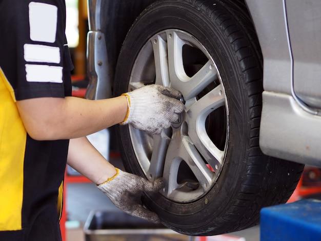 Homme mécanicien en train de réparer la roue d'une voiture en station d'atelier.