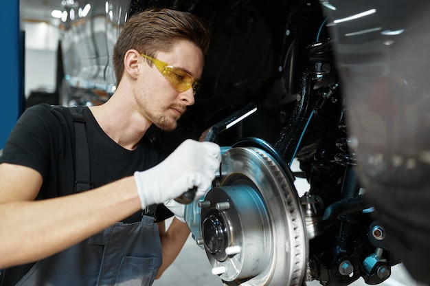 L'homme mécanicien vérifie le disque de frein en atelier mécanique