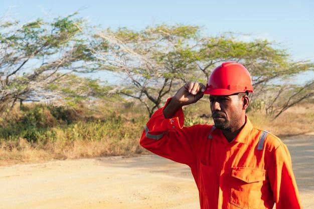 Homme mécanique africain mettant son casque. concept d'ingénieur ou de technicien.