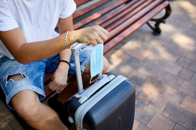 Homme méconnaissable assis sur le banc et masque de protection avec une valise et un mobile
