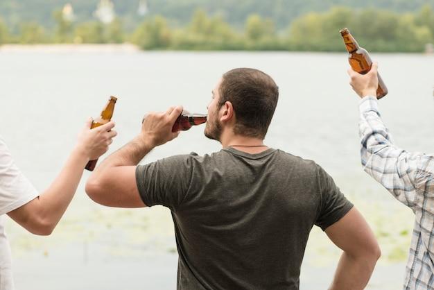 Homme méconnaissable, boire de la bière près de l'eau avec des amis