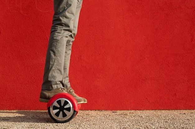 Homme méconnaissable chevauchant un mini hoverboard rouge. mur rouge sur fond