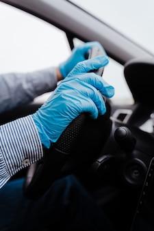 Homme méconnaissable conduisant une voiture portant un masque et des gants de protection