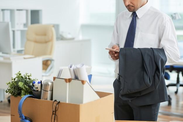 Homme méconnaissable debout au bureau et utilisant un smartphone, avec ses effets personnels dans une boîte