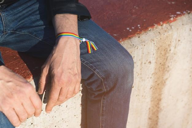 Homme méconnaissable en jeans et veste en cuir noir assis sur un banc en béton avec bracelet de fierté gay arc-en-ciel