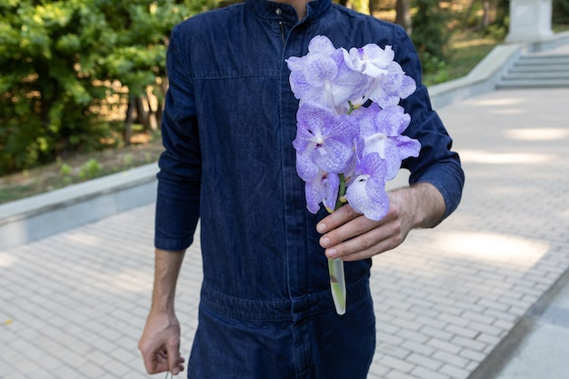Un homme méconnaissable porte un bouquet d'orchidées vanda coerulea dans la rue le jour de l'été. cadeau pour rendez-vous romantique