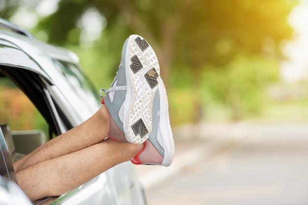 Homme méconnaissable qui sort les pieds en baskets par la fenêtre de la voiture