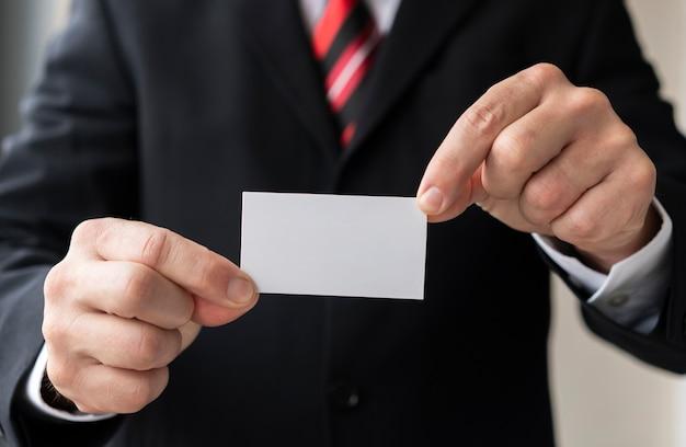 Homme méconnaissable tenant une carte de visite vierge