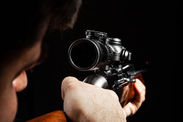 Homme méconnaissable visant avec un fusil de chasse dans l'obscurité close up