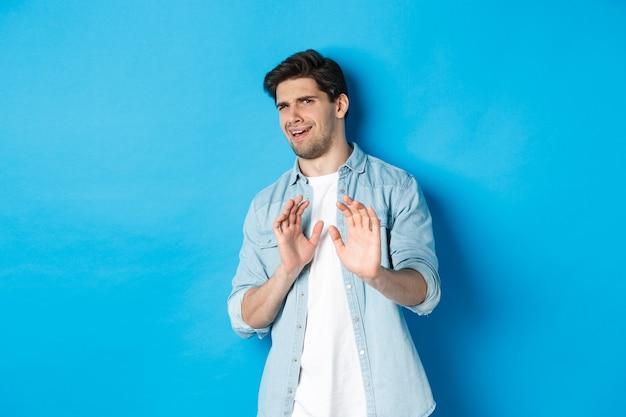 Homme mécontent refusant, disant non et reculant devant quelque chose de dégoûtant, debout sur fond bleu