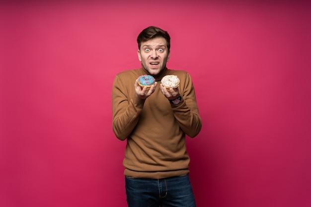 Un homme mécontent tient deux beignets savoureux, se sent malheureux de ne pas manger de bonbons, isolé sur fond rose. homme stressé confus.