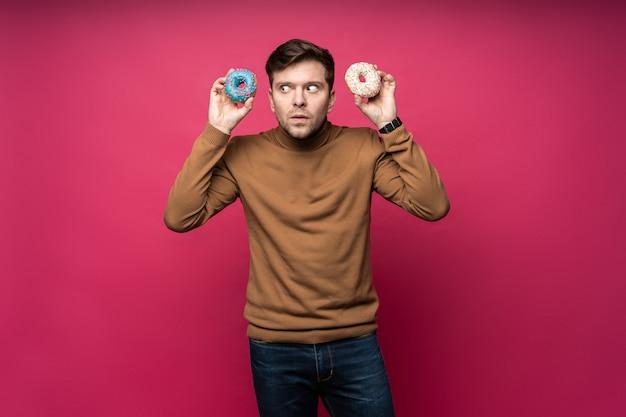 Un homme mécontent tient deux beignets savoureux, se sent malheureux de ne pas manger de bonbons, isolé sur fond rose.