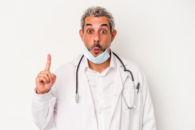 Homme médecin d'âge moyen portant un masque pour virus isolé sur fond blanc ayant une bonne idée, concept de créativité.