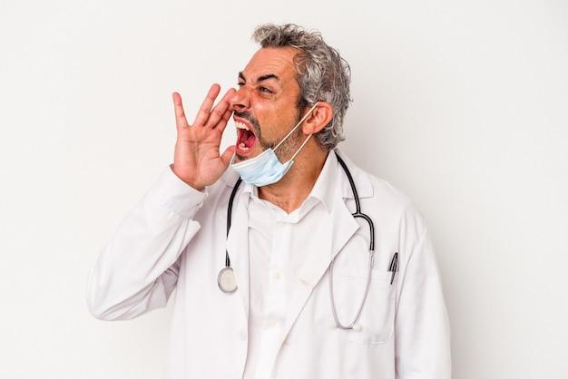 Homme médecin d'âge moyen portant un masque pour virus isolé sur fond blanc criant et tenant la paume près de la bouche ouverte.