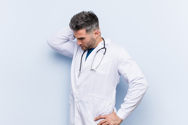 Homme médecin beau jeune toucher l'arrière de la tête, penser et faire un choix.