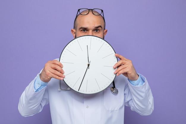 Homme médecin en blouse blanche avec stéthoscope autour du cou tenant une horloge devant son visage à l'air inquiet