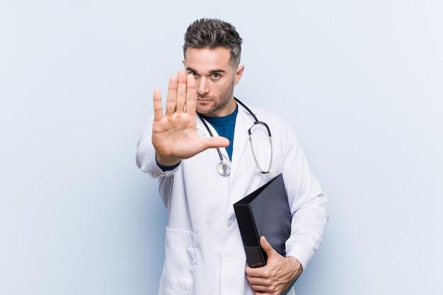 Homme médecin caucasien tenant un dossier debout avec la main tendue montrant le panneau d'arrêt, vous empêchant.