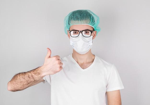 Homme médecin chirurgien américain sur fond gris à la recherche et montrant le signe correct.