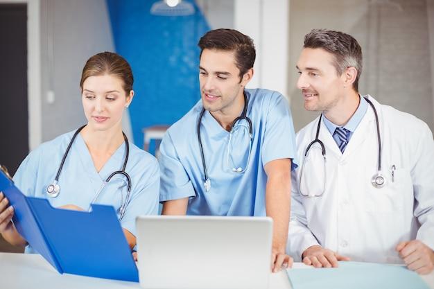 Homme médecin et collègues avec le presse-papiers tout en discutant