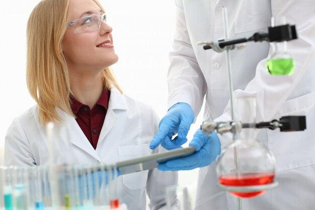 Un homme médecin dans un laboratoire de chimie tient une tablette dans sa main avec écran