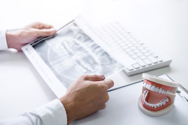 Homme médecin ou dentiste travaillant avec un film radiographique dentaire