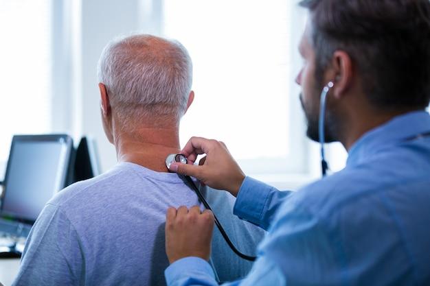 Homme médecin examine un patient