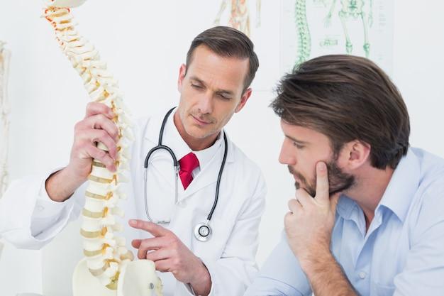 Homme médecin expliquant la colonne vertébrale à un patient