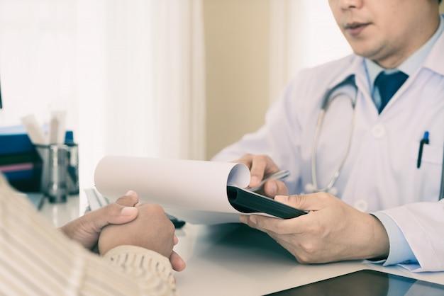 Homme médecin expliquant le diagnostic au patient. patiente à la recherche inquiète lors de l'écoute de nouvelles au lit.