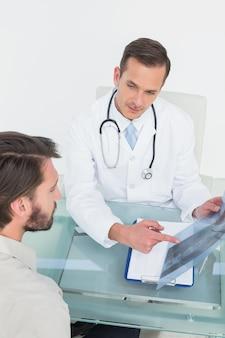 Homme médecin expliquant la radiographie de la colonne vertébrale au patient
