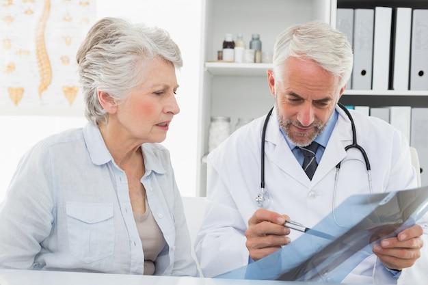Homme médecin expliquant rapport de radiographie à un patient senior