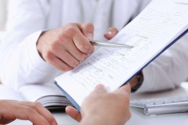 Homme médecin main tenir un stylo argenté et montrant le tampon.