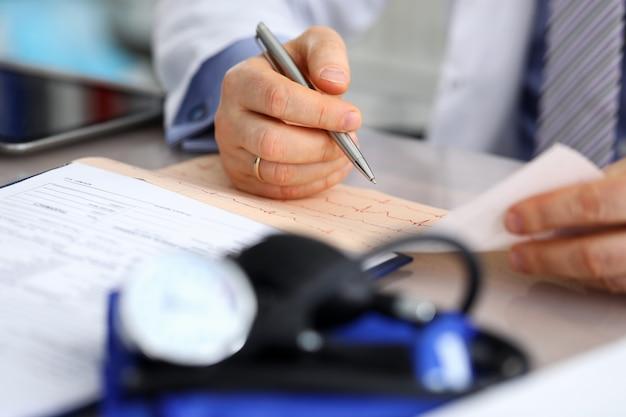 Homme médecin mains avec graphique cardiogramme