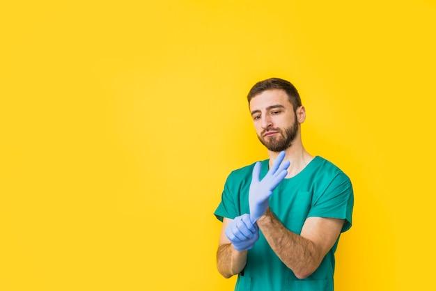 Homme médecin met des gants stériles