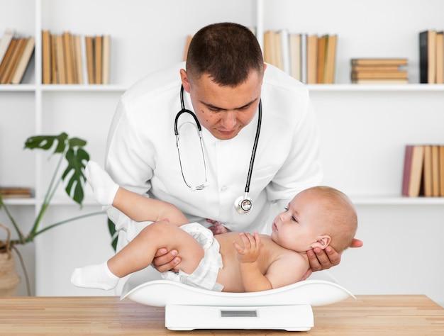 Homme médecin mettant bébé patient à l'échelle