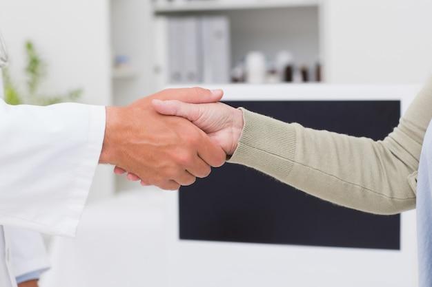 Homme médecin et patiente se serrant la main