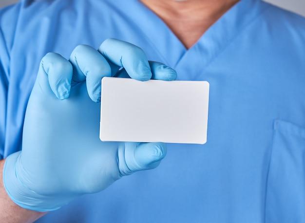 Homme médecin portant des gants en latex bleus tient une carte de visite de papier blanc vierge