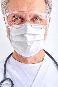 Homme médecin ridé avec des yeux perçants regarde la caméra, un médecin âgé sauve la vie, portrait