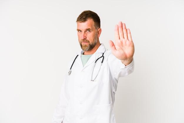 Homme médecin senior isolé sur blanc debout avec la main tendue montrant le panneau d'arrêt, vous empêchant.