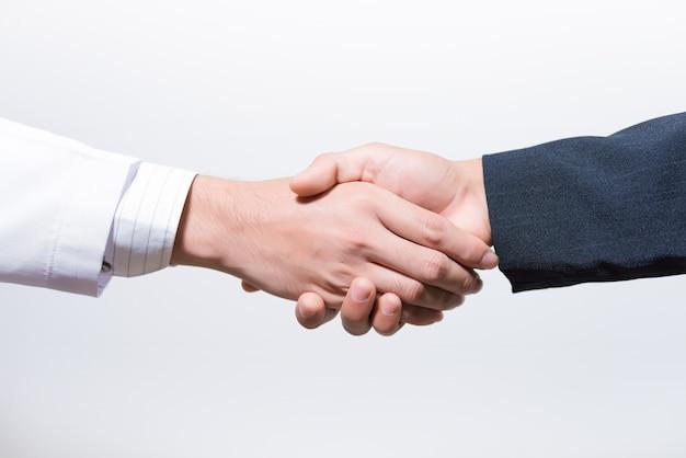 Homme médecin et son avocat se serrant la main sur blanc.